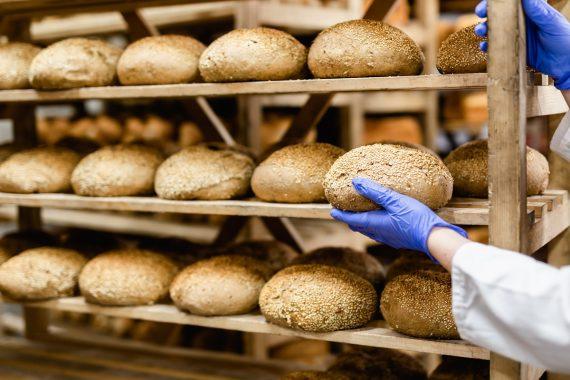Kuvituskuva, leipuri ottaa leivän leipähyllyltä